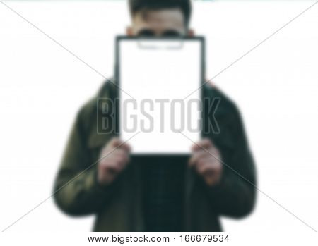 Blurred defocused photo of the yung man holding a white empty paper ion white isolated background