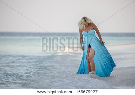 Blonde woman in long dress is walking on the beach