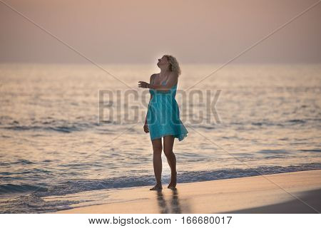 Blonde girl is walking on the Maldivian beach and watching the sunrise