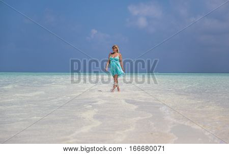 Pregnant woman is walking on Maldives island