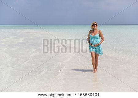 Pregnant woman is holding her belly and walking on the sand bank