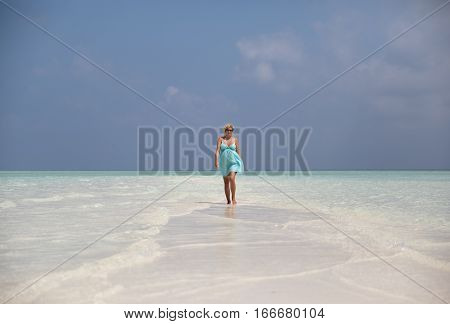 Beautiful pregnant woman is walking on sand bank Maldives