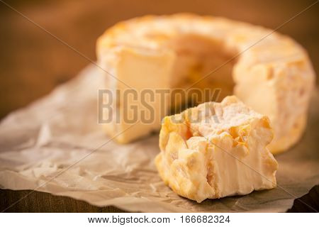 Portion Cut From Whole Golden Camembert Cheese On Crumpled Paper Sheet