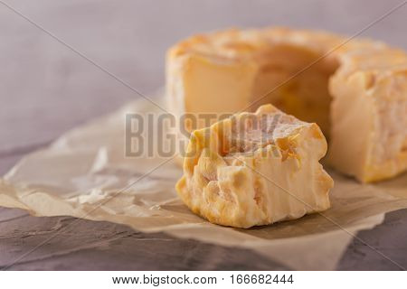 Portion Cut From Whole Golden Camembert On Grey Board