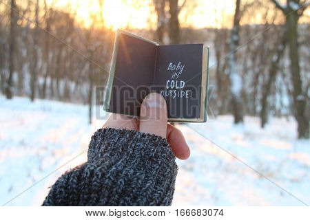 Baby its cold outside. Hand holding a book with the inscription.