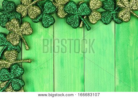 St Patricks Day Corner Border Of Shiny Glitter Shamrocks Over A Green Wood Background