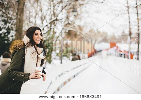 Happy Woman With A Cup Of Hot Drink On  Cold Winter Outdoors