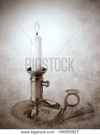 Vintage brass candlestick with burning candle and snuffer vignette and duotone effect