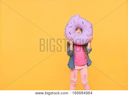 Surprised happy little girl playing with big toy in shape of donut, hiding and looking through a hole like zero numeral over yellow color background