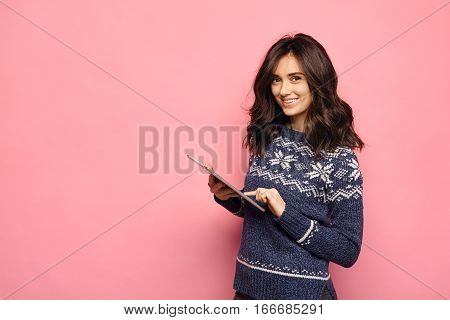 Beautiful brunette girl using tablet computer at pink color background. Young woman wearing christmas sweater browsing internet or using app