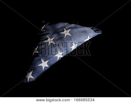 Closeup of a worn American flag on a black background