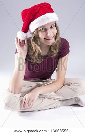 Happy and smiling Teenage Girl in Santa Hat Wearing Dental Teeth Brackets. Sitting Against White Background. Vertical Image Orientation