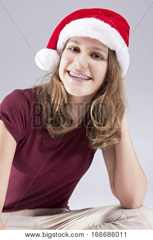 Dental Concepts and Ideas. Happy Caucasian Teenager in Santa Hat With Teeth Brackets. Sitting. Vertical Image Composition