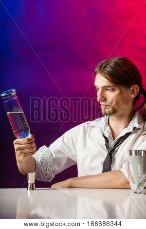Alcohol liquor entertainment relax bartending concept. Barman fills shot glass. Young male bartender makes a drink.