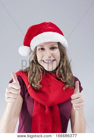 Dental Treatment Concepts. Happy Smiling Caucasian Teenager in Santa Hat With Teeth Brackets Posing Against White Background. Vertical Image