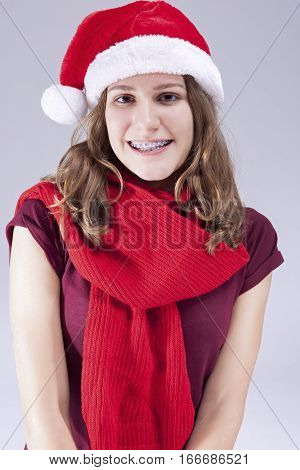 Dental Treatment Concepts and Ideas. Caucasian Teenager in Santa Hat With Teeth Brackets Against White. Vertical Image Composition
