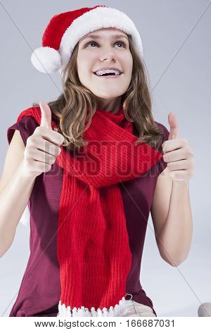 Dental Treatment Concepts. Happy Smiling Caucasian Teenager in Santa Hat With Teeth Brackets Posing Against White Background. Vertical Image Composition