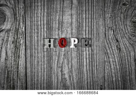 Grey wooden background with the word hope black and white toning