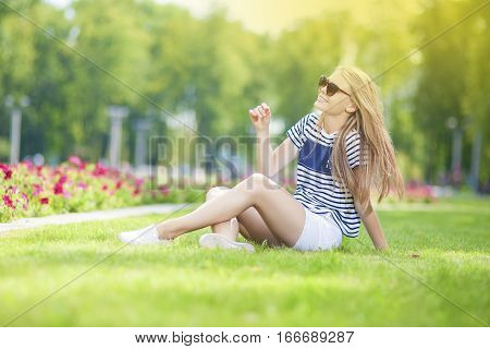 Cute and Happy Caucasian Blond Teenage Girl Posing on the Grass in Green Flowery Summer Park in Sunglasses. Horizontal Image Orientation