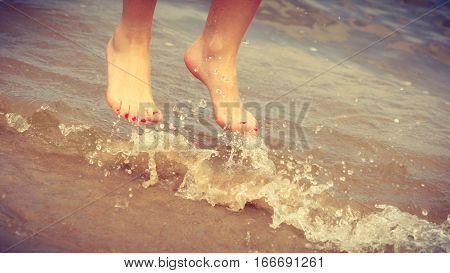 Happiness and craziness. Female legs feet in air jump on beach over water. Fun and freedom.