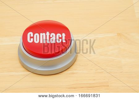 A Contact red push button A red and silver push button on a wooden desk with text Contact