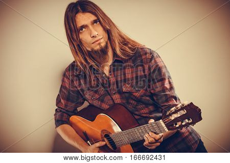 Hobby passion concept. Guitarist is playing the guitar. Long haired performer and his instrument.