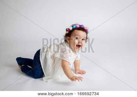 A very excited baby crawls on a white background. Her hand is up and it seems she is about to wave. Her mouth is open in a big smile and she has bright eyes.
