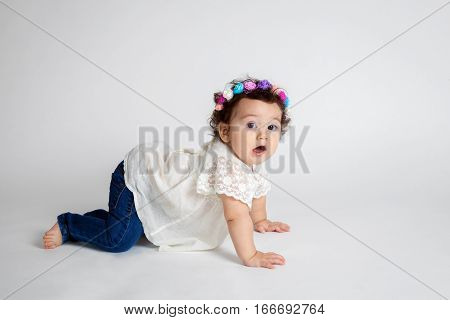 A baby on all fours stops mid crawl to stare blankly at the camera. She has a floral headband and is wearing a white shirt and jeans and is barefoot.