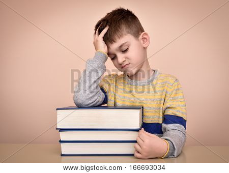 Sad and displeased young boy sitting at the table with books and holding his forehead with one hand