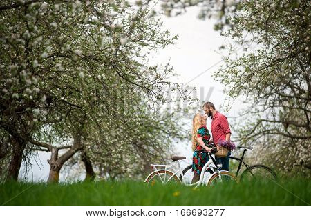 Loving Young Couple With Bicycles In Spring Garden