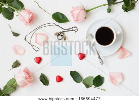 St Valentines day still life - cup of coffee, peach roses, blue sheet of note for St Valentines day message, owl shaped clock, heart shaped candies on white background. Flat lay top view of St Valentines day still life. St Valentines day background in vin