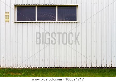 White industrial grooved metal wall with a window and some green grass