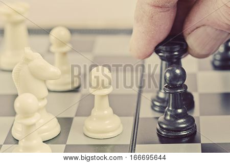 The athlete holds the figure in the background of a chessboard.