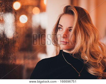Beautiful blonde girl 20-24 year old sitting in cafe over lights background. Looking away. 20s.