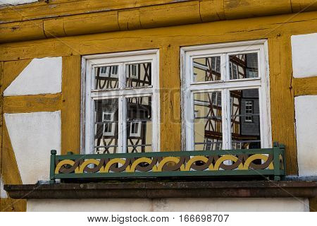 Two windows on old multicolored wooden country house. Windows reflect old houses