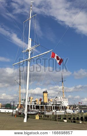 The mast with a flag on a wooden promenade in Halifax (Nova Scotia Canada).