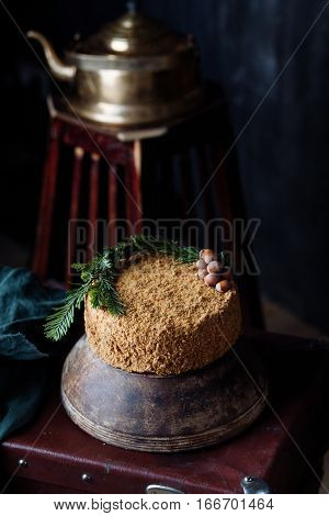 handwork cake with nuts costs on a suitcase. at a background a teapot of copper color