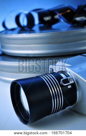 closeup of a retro film camera, some film strips and some metal movie film reel canisters on a table with, a blue toning