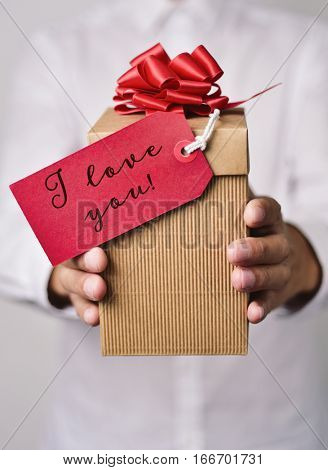 closeup of a young caucasian man in a white shirt holding a gift box with a red label tied to it with the text I love you written in it
