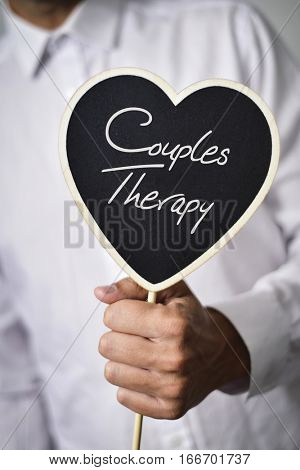 a young caucasian man wearing a white shirt shows a heart-shaped signboard with the text couples therapy written in it