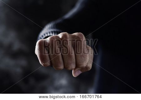 closeup of a young caucasian man in casual wear with a threatening gesture, with his fist clenched and pointing to the observer