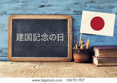 a chalkboard with the text National Foundation Day written in Japanese, a pot with pencils, some books and the flag of Japan, on a rustic wooden desk