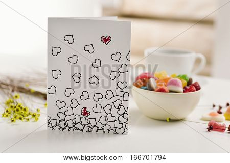 a homemade postcard, made by myself, with some hearts drawn in it, some of them painted red, on a white table next to a cup of coffee, some flowers and a bowl with candies