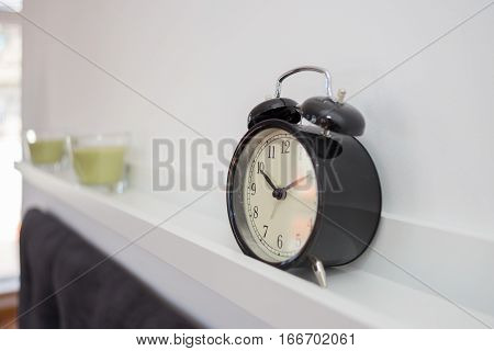 Alarm clock and candles on a shelve