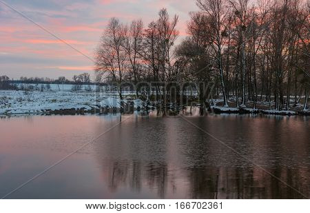 Pictorial evening landscape with small river Hrun' at winter sunset time in Poltavskaya oblast Ukraine