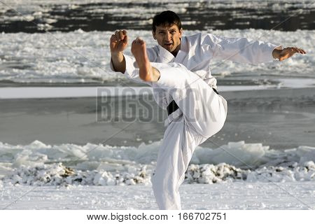 Man in white kimono is practicing karate shot barefoot in the snow outdoors at winter.