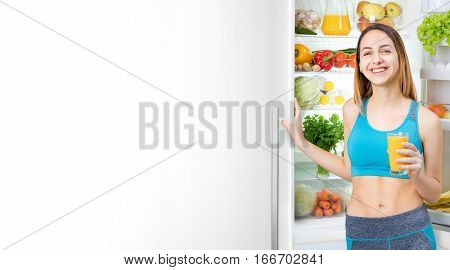 Young woman drinking juice and staying near the fridge full of health food. Fitness and healthy lifestyle concept.