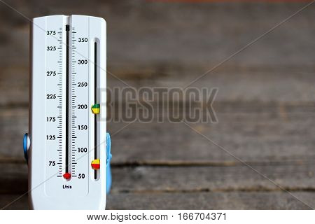 Peak flow meter isolated on wooden background. Hand medical device used to monitor the breath of a person suffering from bronchial asthma. Peak flow meter wide range of values. Closeup