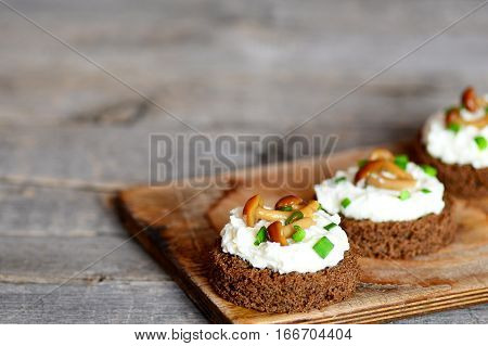 Vegetarian canape with soft cheese and mushrooms on a board on a wooden table. Canape cooked from brown bread, soft cheese and conserved mushrooms. Simple holiday appetizer. Closeup