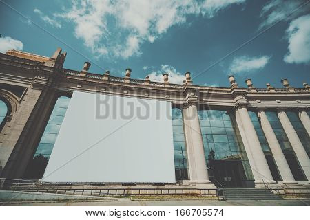 White huge mock up banner for your advertising on facade of building with columns blank big billboard with copy space area for your text message or promotional content on house on sunny day